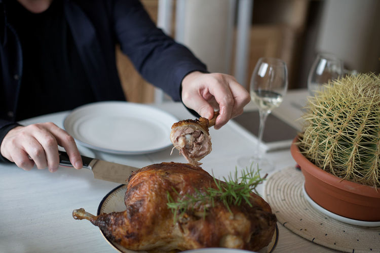 Dinner Dinner Time Thanksgiving Turkey Adult Food Food And Drink Freshness Glass Hand Herb Holding Human Body Part Human Hand Indoors  Lifestyles Meat Men Midsection One Person Party Plate Preparation  Real People Table
