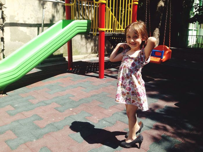Full length of smiling girl wearing high heels while standing at playground