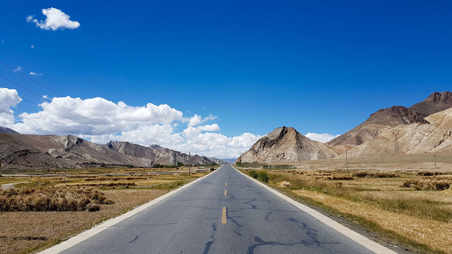 Road amidst landscape against blue sky