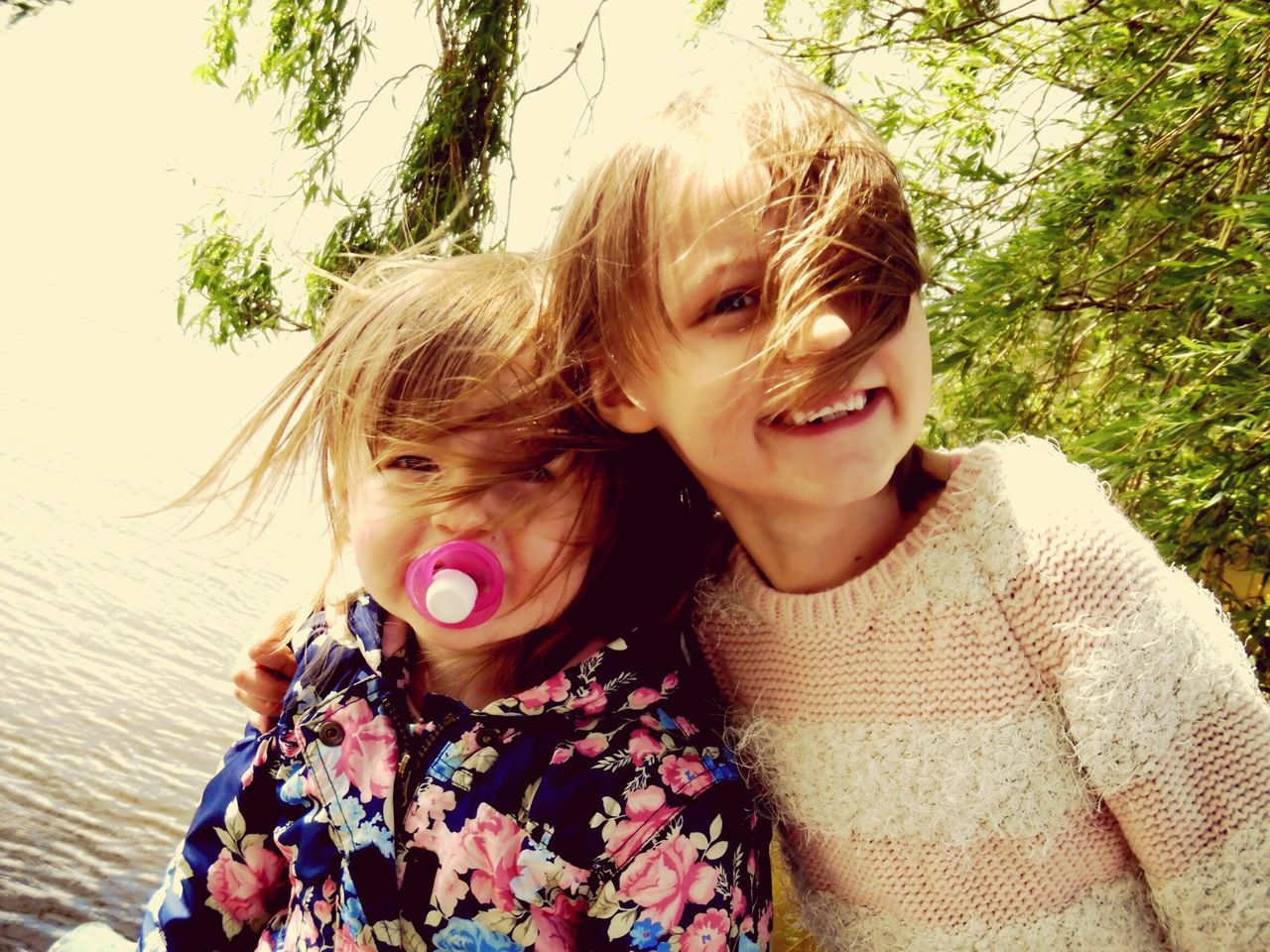 two people, emotion, real people, child, childhood, women, portrait, togetherness, girls, bonding, smiling, happiness, front view, females, lifestyles, family, love, leisure activity, positive emotion, hair, outdoors, innocence, warm clothing, sister, hairstyle