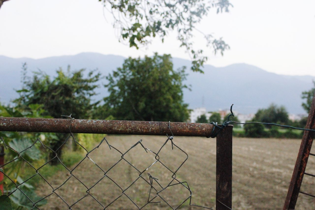 fence, barrier, boundary, security, protection, metal, safety, sky, focus on foreground, no people, nature, tree, wire, plant, day, barbed wire, mountain, outdoors, tranquility, close-up