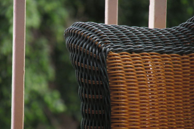 Cropped image of whicker chair by railing
