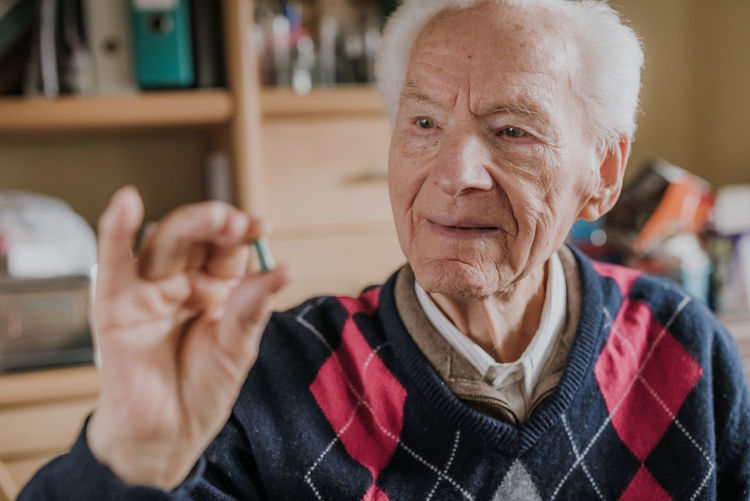 Senior man holding medicine at home