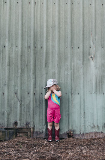 Full length of girl looking away while standing on wood