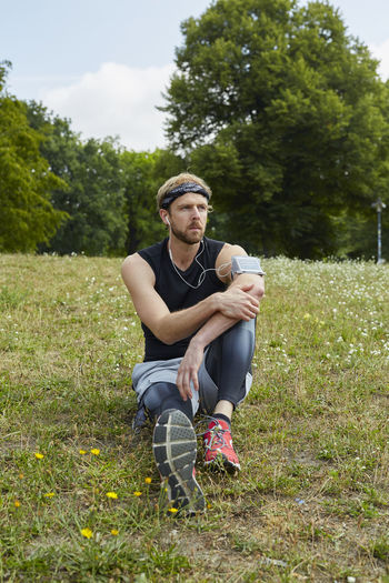 Man listening music while sitting on grassy land in park