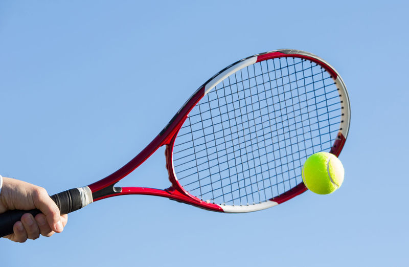 Cropped hand holding racket against clear blue sky during sunny day