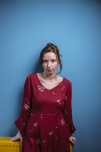 Portrait of woman standing against blue wall