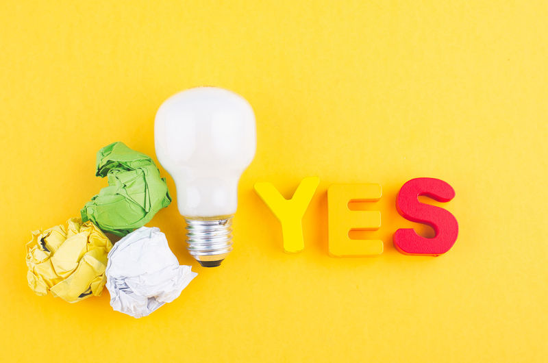 word YES, crumple paper and bulb over yellow background Yellow Studio Shot Indoors  Still Life Copy Space No People Text Communication Table Close-up Western Script Colored Background Yellow Background Multi Colored Food And Drink High Angle View Sweet Food Capital Letter Food