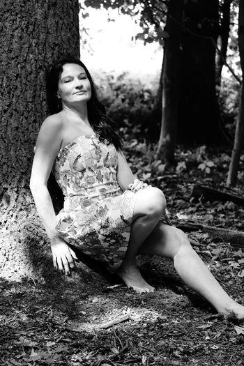 Portrait of beautiful woman sitting by tree