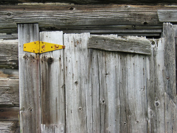 Close-Up Of Yellow Hinge On Old Wooden Door