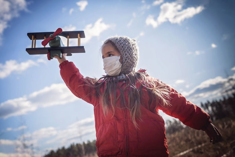 Cute girl wearing respirator mask staying on the meadow with airplane in her hand