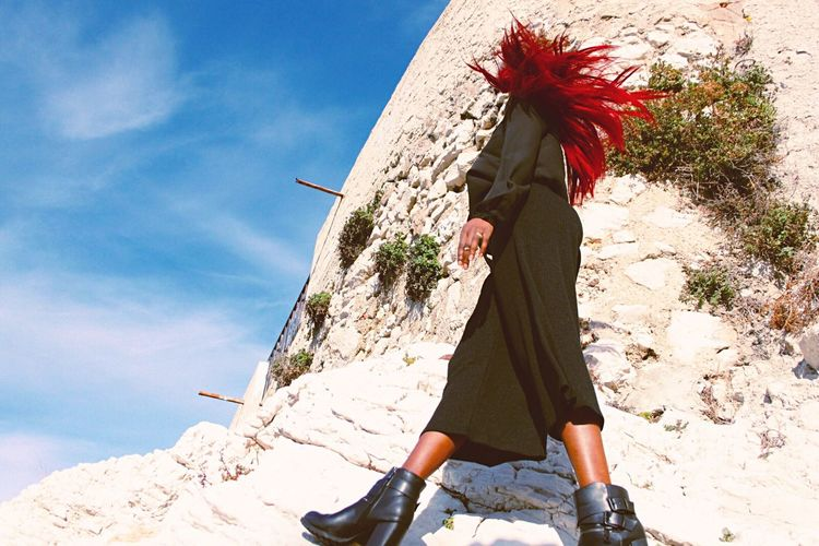 Low angle view of woman walking by wall against clear sky