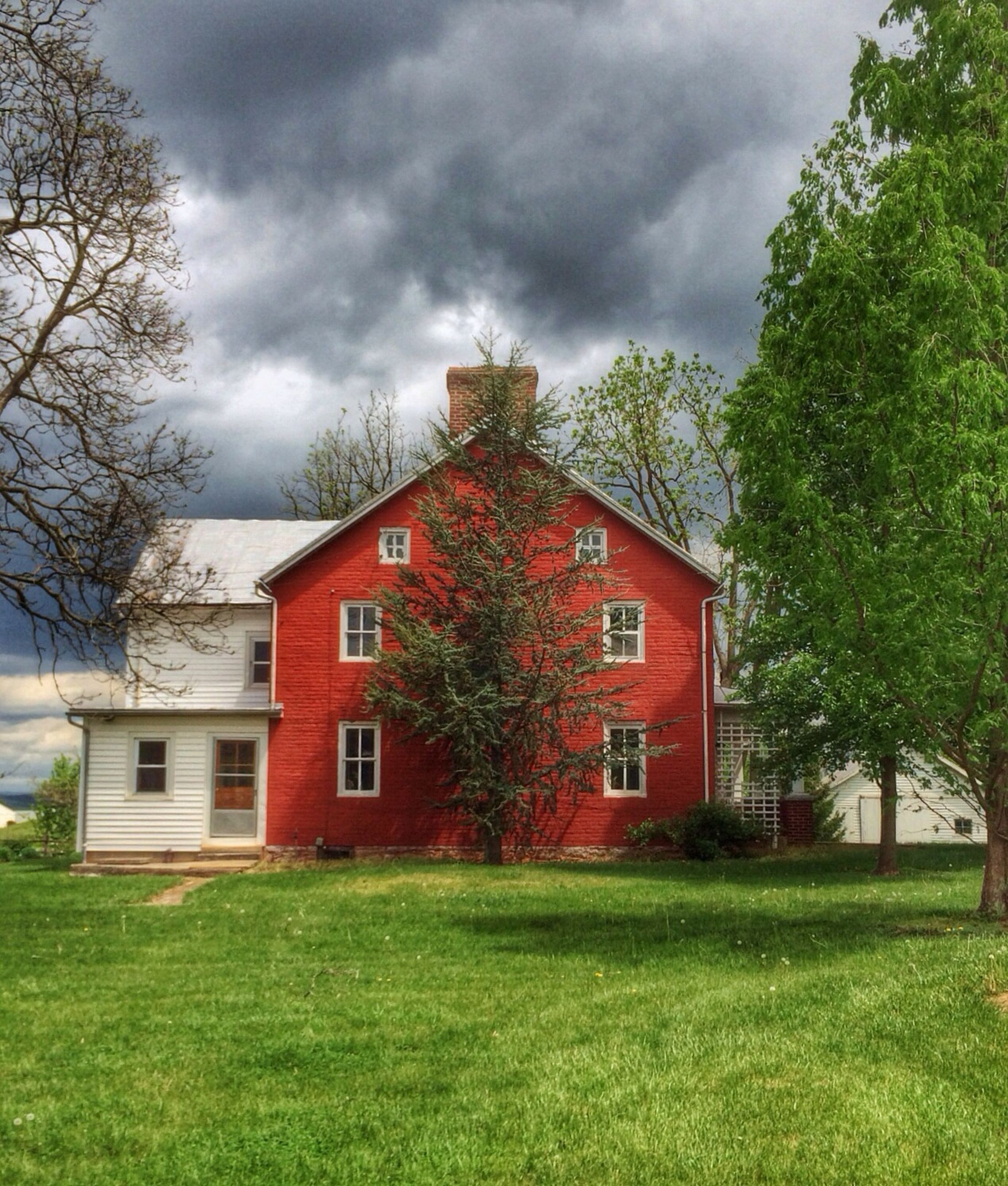 building exterior, architecture, tree, built structure, sky, cloud - sky, house, cloudy, growth, grass, green color, nature, beauty in nature, red, cloud, overcast, weather, residential structure, plant, day
