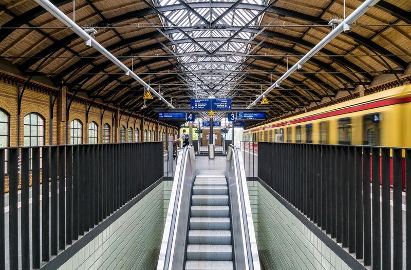Escalator amidst railings at railroad station