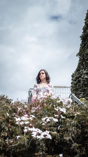 Low angle view of woman looking away while standing by plants against sky