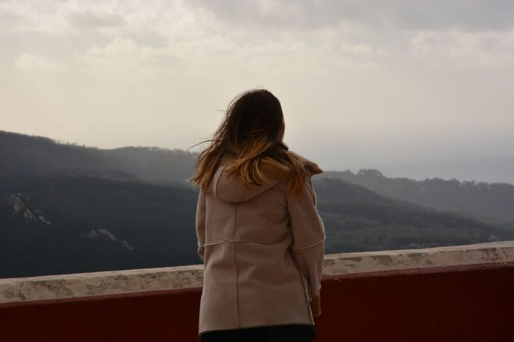Rear view of woman standing by wall against mountains