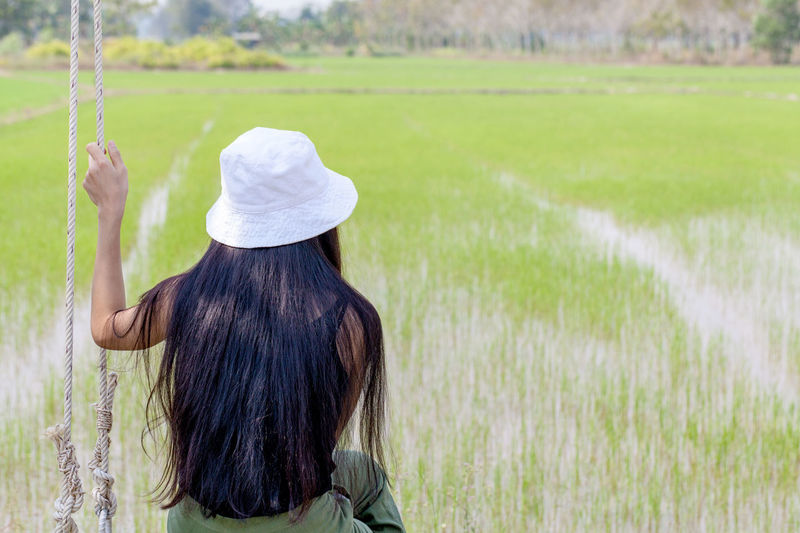 Rear View Of Woman Sitting By Rice Field