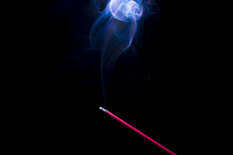 Incense and smoke against black background