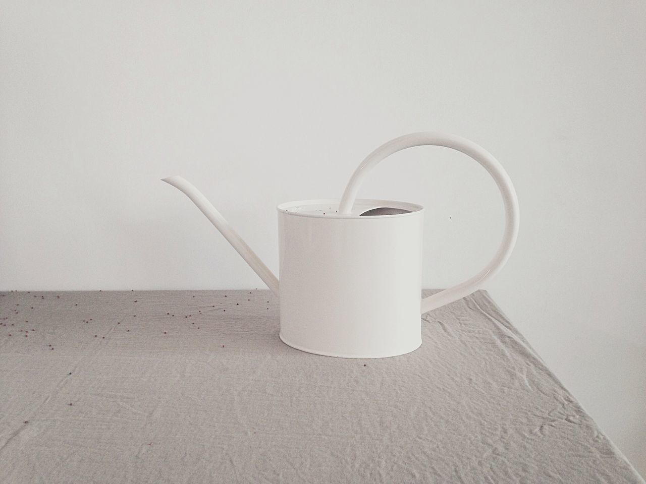 Watering can on table against wall