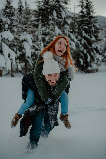 Man carrying woman on back on snow covered land