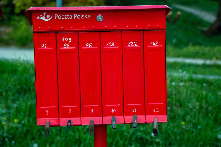 Close-up Communication Correspondence Day Focus On Foreground Grass Green Color In A Row Letter Mail Mailbox Nature No People Number Outdoors Plant Post Box  Public Mailbox Red Text Western Script