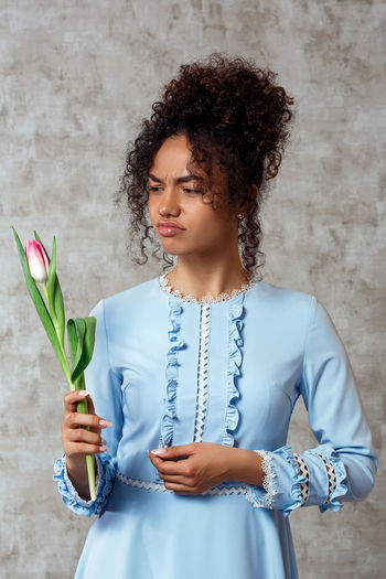 Sad young woman holding flower while standing against wall