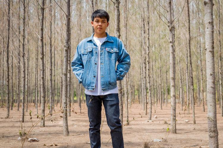 Portrait of teenage boy standing in forest