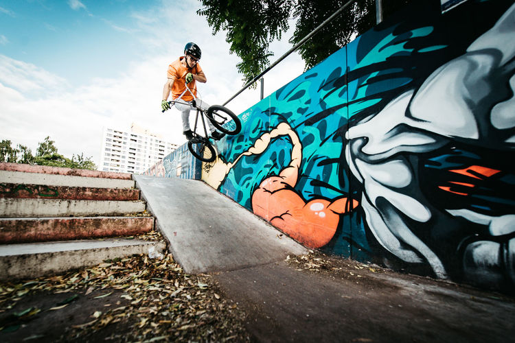 Full Length Graffiti One Person Real People Low Angle View Day Leisure Activity Sky Young Adult Nature Lifestyles Skateboard Park Casual Clothing Men Outdoors Creativity Jumping Adult Architecture Skill  Bmx  Bmx Cycling