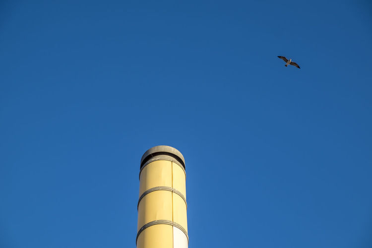Low angle view of bird flying over smoke stack against clear blue sky