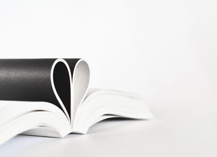 Pages of book in heart shape over white background