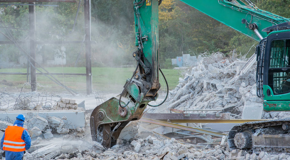 Excavator by demolished built structure