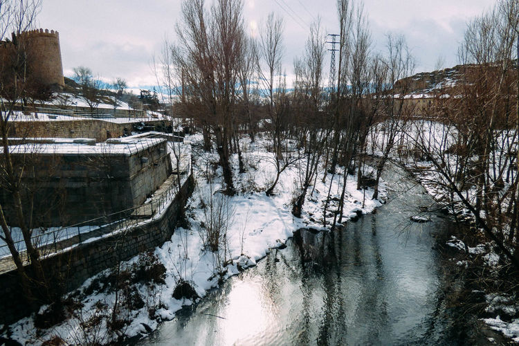 Scenic view of frozen river against sky during winter