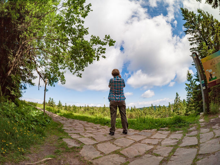 Rear view of man standing by footpath against sky