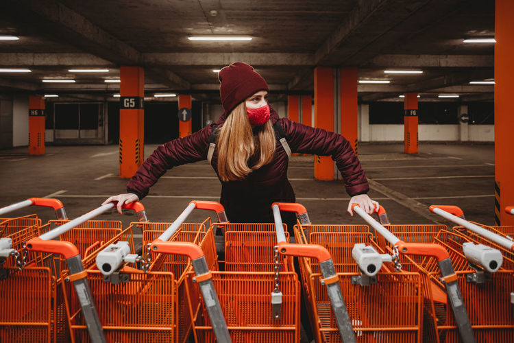 Woman with mask holding row of orange shopping carts in garage