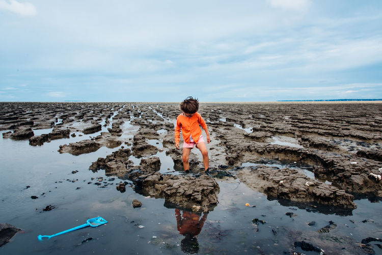 Girl Standing On Mud Against Sky