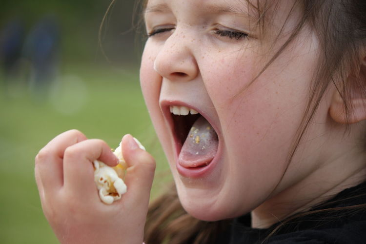 Close-up of girl eating popcorns while standing outdoors