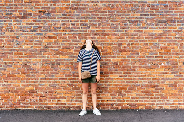 Full Length Of Teenage Girl Standing Against Brick Wall