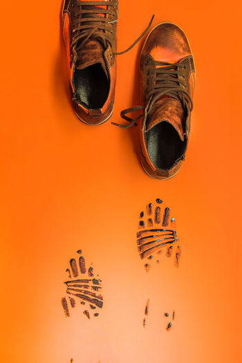 High angle view of shoes on orange table