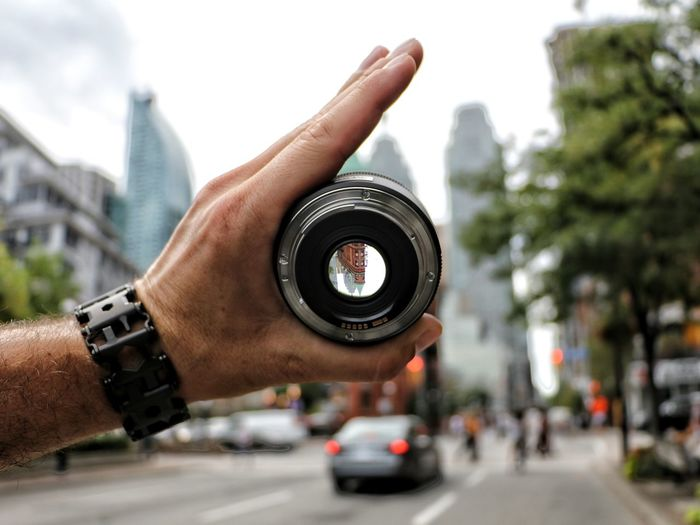 Cropped image of hand holding lens on city street