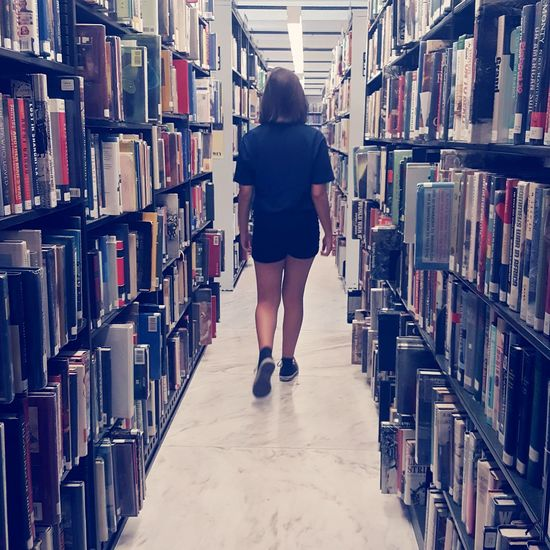 Walls of Books - Library Shelf Bookshelf Research Education Book Indoors  Full Length One Person Rear View Choice Learning Only Women People Adult One Woman Only Adults Only Large Group Of Objects Storage Compartment Information Medium