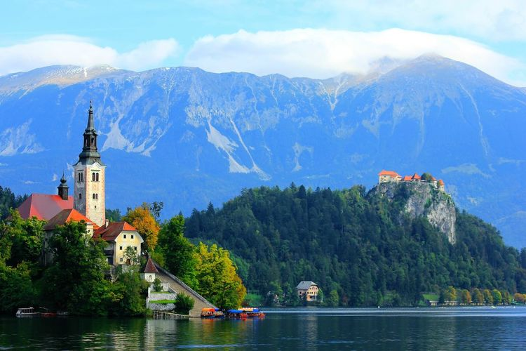 Lake bled by church against rocky mountains