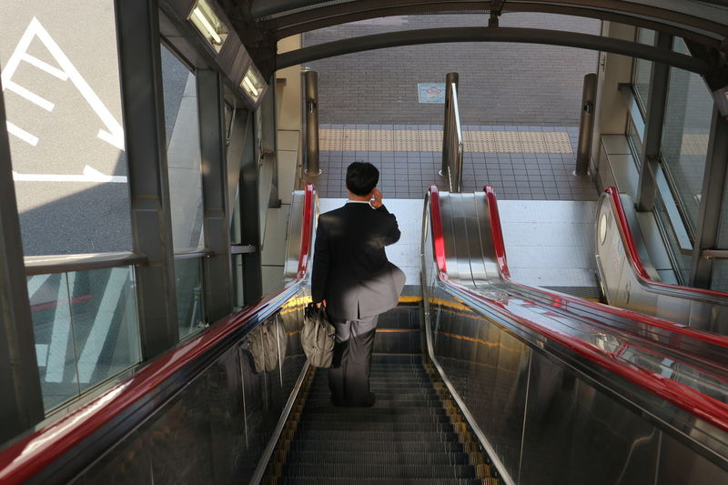 working man on escalator Standing Working Escalator Lifestyles Men Mode Of Transportation Motion on the move One Person Public Transportation Railing Real People Rear View Transportation Walking