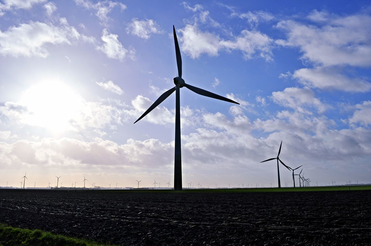 Low Angle View Of Silhouette Windmills On Field Against Sky