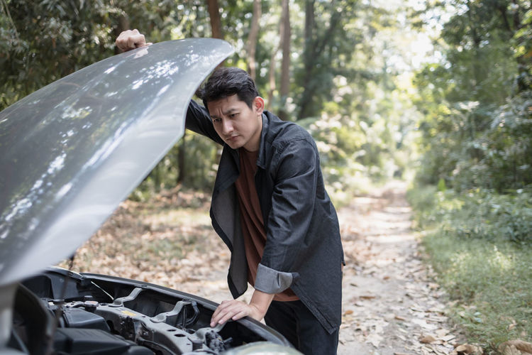 Young man standing on car in forest