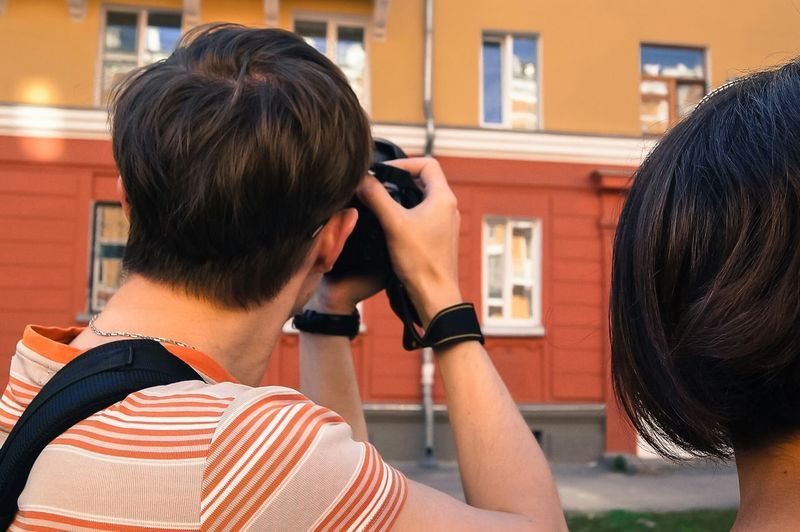 Rear view of man and woman photographing in front of building