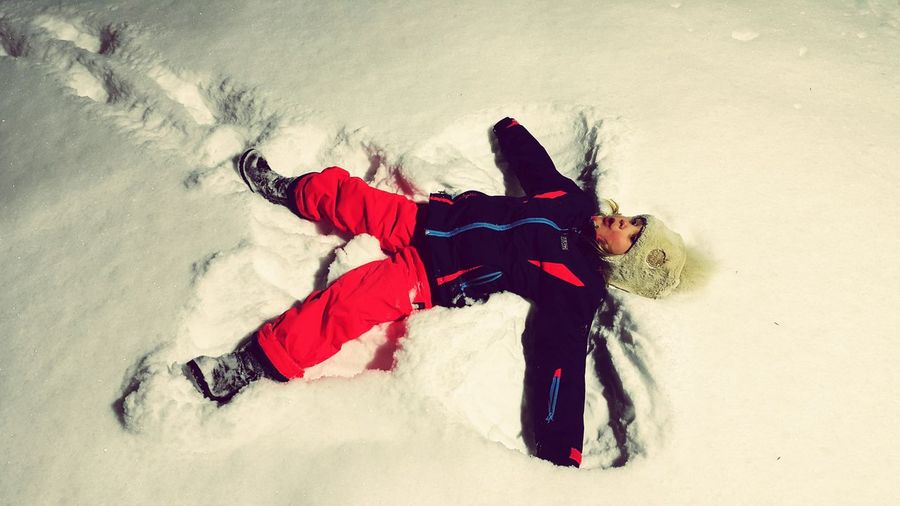 High angle view of girl making snow angel