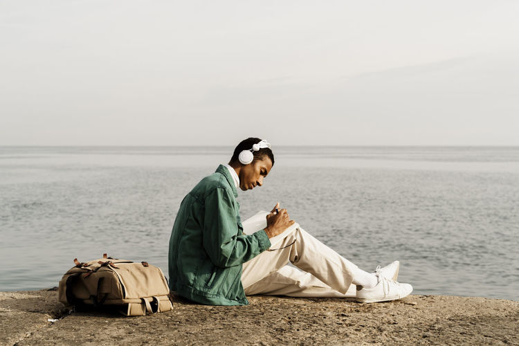 Side view of man sitting on beach against sea
