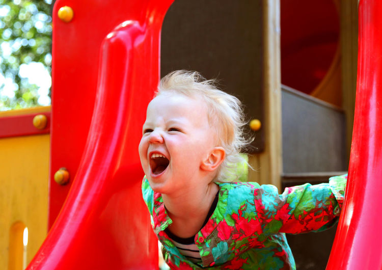 Cute girl laughing in red playground