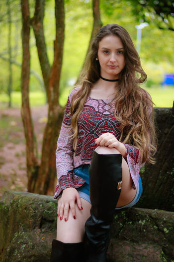 Beautiful Woman Casual Clothing Day Focus On Foreground Front View Leisure Activity Lifestyles Looking At Camera Nature One Person Outdoors Portrait Posing Real People Standing Technology Three Quarter Length Tree Tree Trunk Wireless Technology Young Adult Young Women