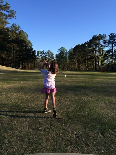 A perfect follow through! Blue Casual Clothing Childhood Clear Sky Elementary Age Field Full Length Girls Golfing Grass Innocence Leisure Activity Lifestyles Nature Park - Man Made Space Playing Rear View Relaxing Sport Taking Photos Tree Walking